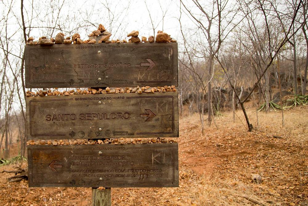 Placas indicativas das trilhas em Juazeiro do Norte, cheias de pedras levadas pelos romeiros de Padre Cícero durante a romaria de Finados