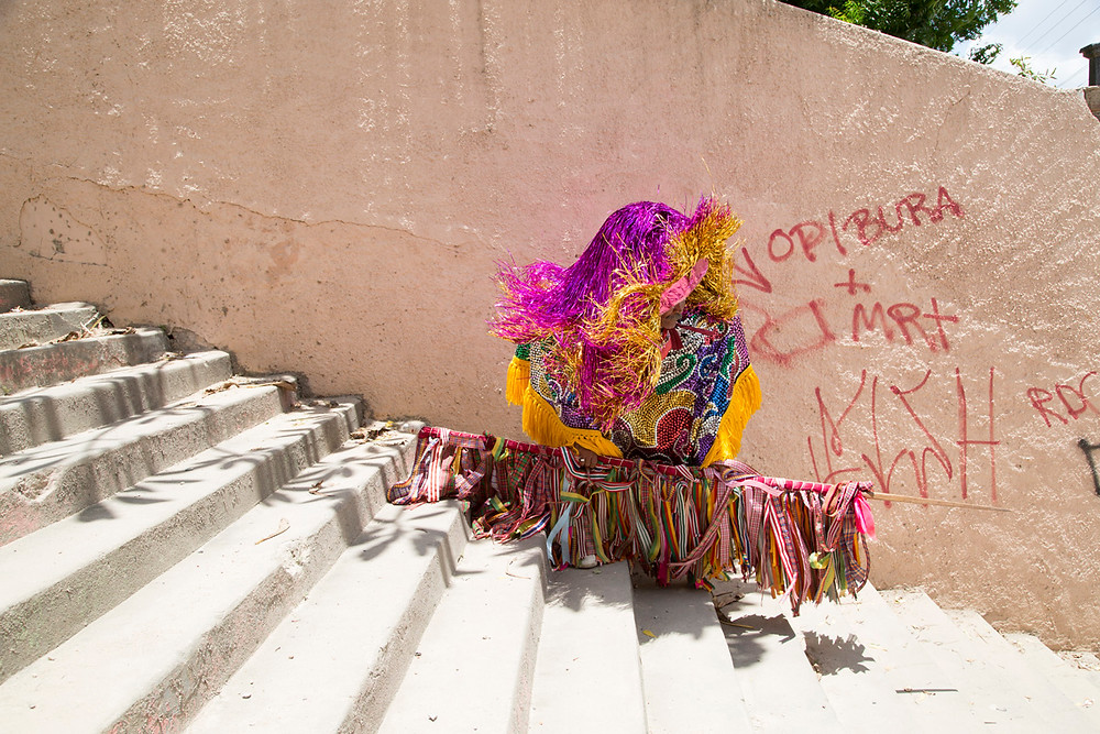 Caboclo de lança desce a escadaria na cidade de Nazaré da Mata e se encaminha para a concentração, onde os outros membros do seu grupo esperam por sua vez de se apresentar na brincadeira de Carnaval conhecida como Maracatu Rural ou Maracatu do Baque Solto