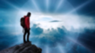 Man on Mountain Looking Into Clouds.jpg