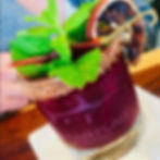 Purple cocktail with mint garnish in glass with bear flag fish co logo.