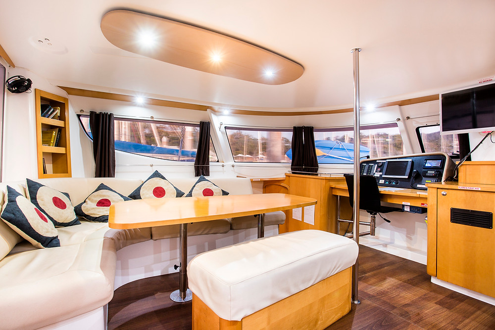 The indoor living area of a Whitsunday bareboat catamaran or yacht is called a saloon. It contains living, dining and kitchen in one