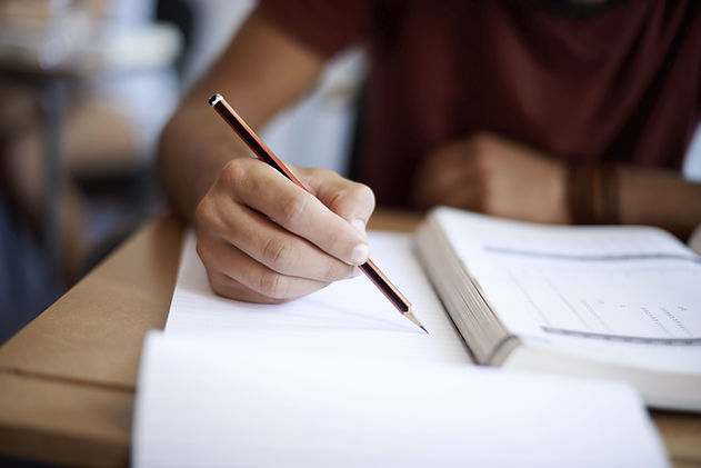 male in a burgundy shirt with his hand resting on a textbook while holding a brown pencil with a sharpened lead point
