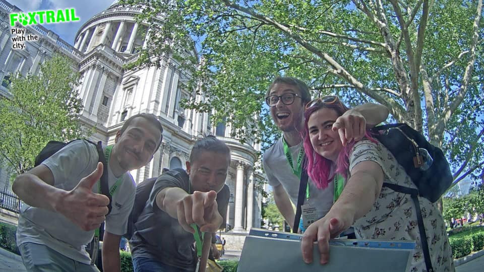 3 guys and a girl (with pink hair) pointing at the camera, with St Paul's Cathedral in the background