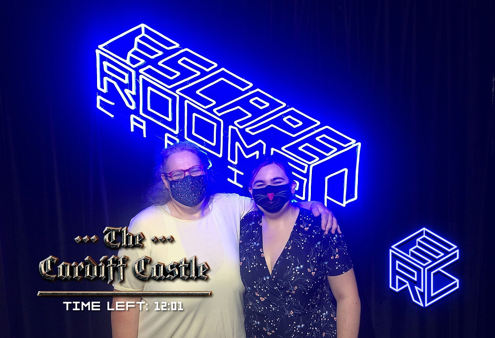 """Two women stand in front of a neon blue sign reading """"Escape Rooms Cardiff"""""""