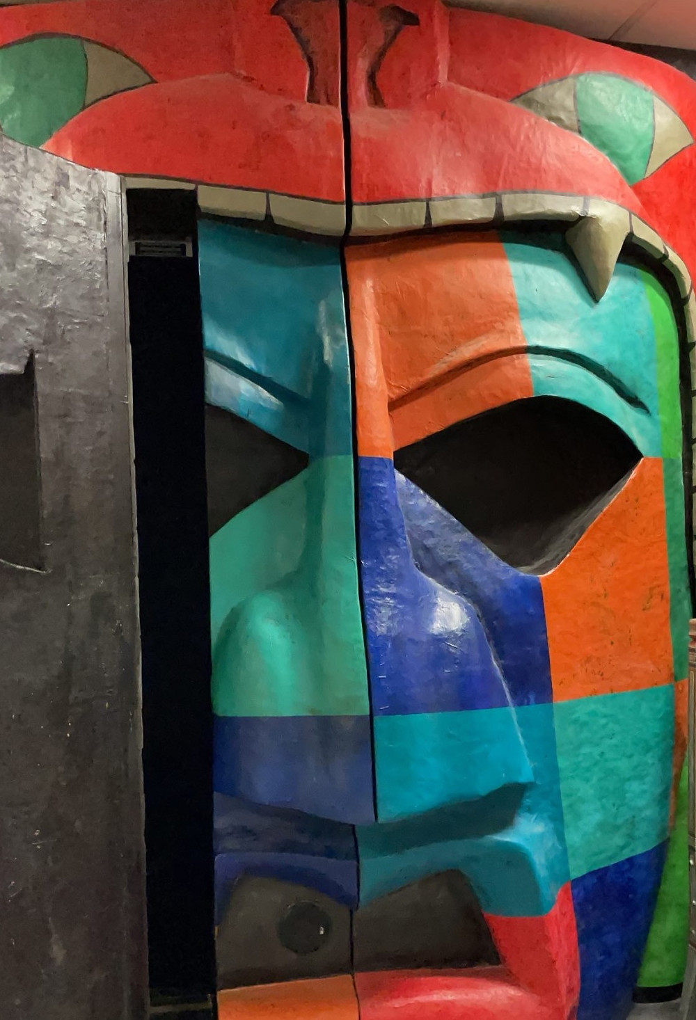 A large colourful Mayan statue, with a door in the left eye