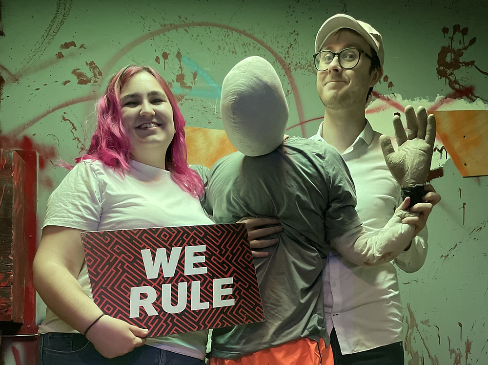 """The team holding a board saying """"we rule"""" and a mannequin"""