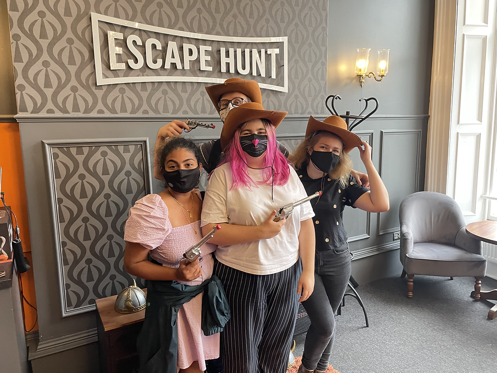 3 girls and a guy wear cowboy hats in front of an 'Escape Hunt' logo
