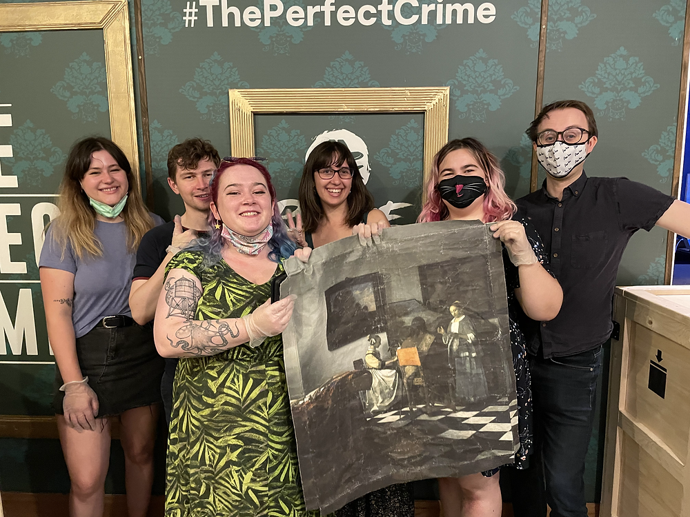 A team of 2 guys and 4 girls hold up a painting