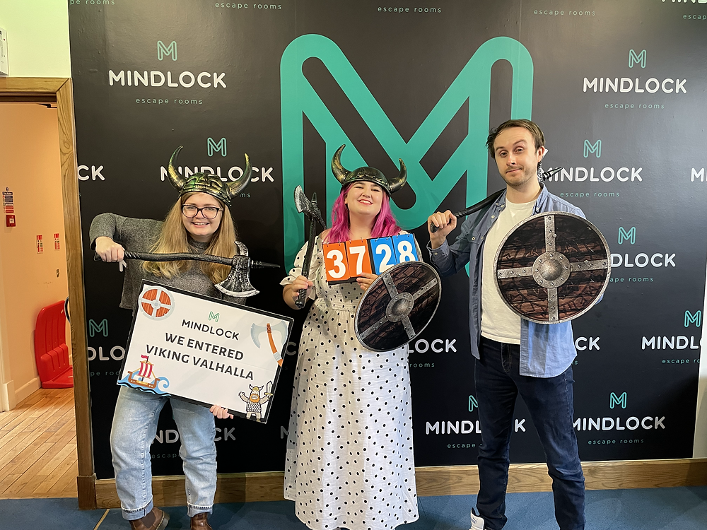Two girls and a guy pose with viking helmets, shields and axes. One holds a sign reading 'We entered viking valhalla' and the other holds a time board reading '37:28'