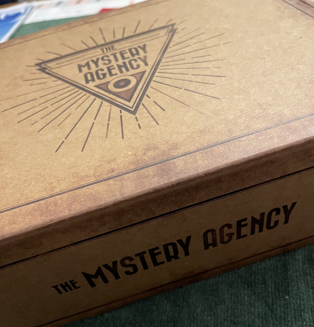 """A brown box with """"The Mystery Agency"""" written on the top (within a triangle with rays coming out of it) and on the side"""