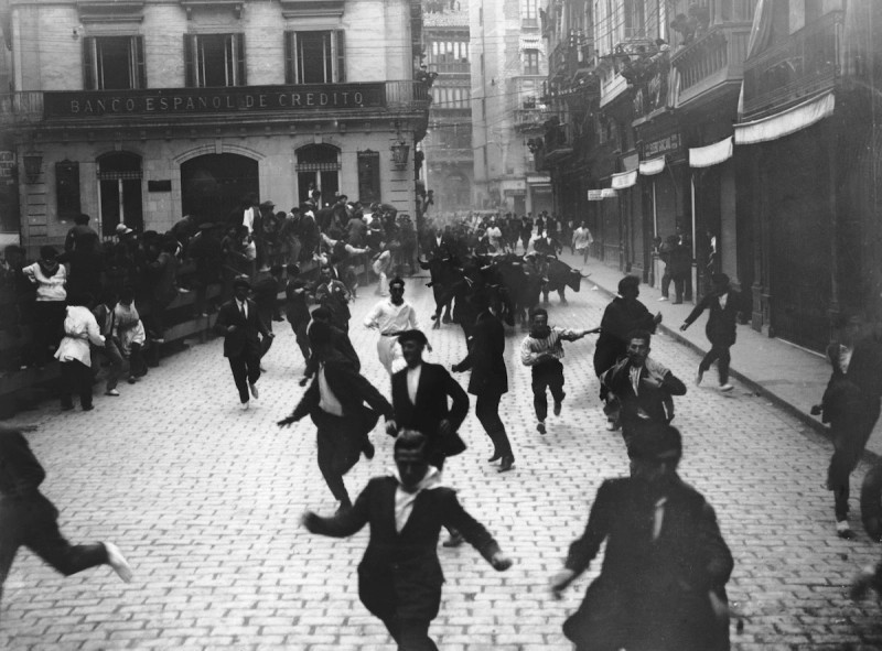 people running from a bull in the street