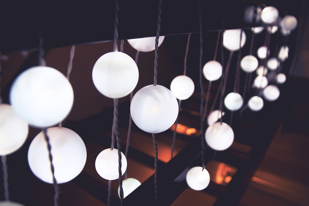 White circular light bulbs illuminated as they hang from the ceiling.