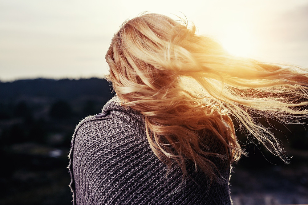 Back view of a blonde lady in a grey jumper with a sunset in the background