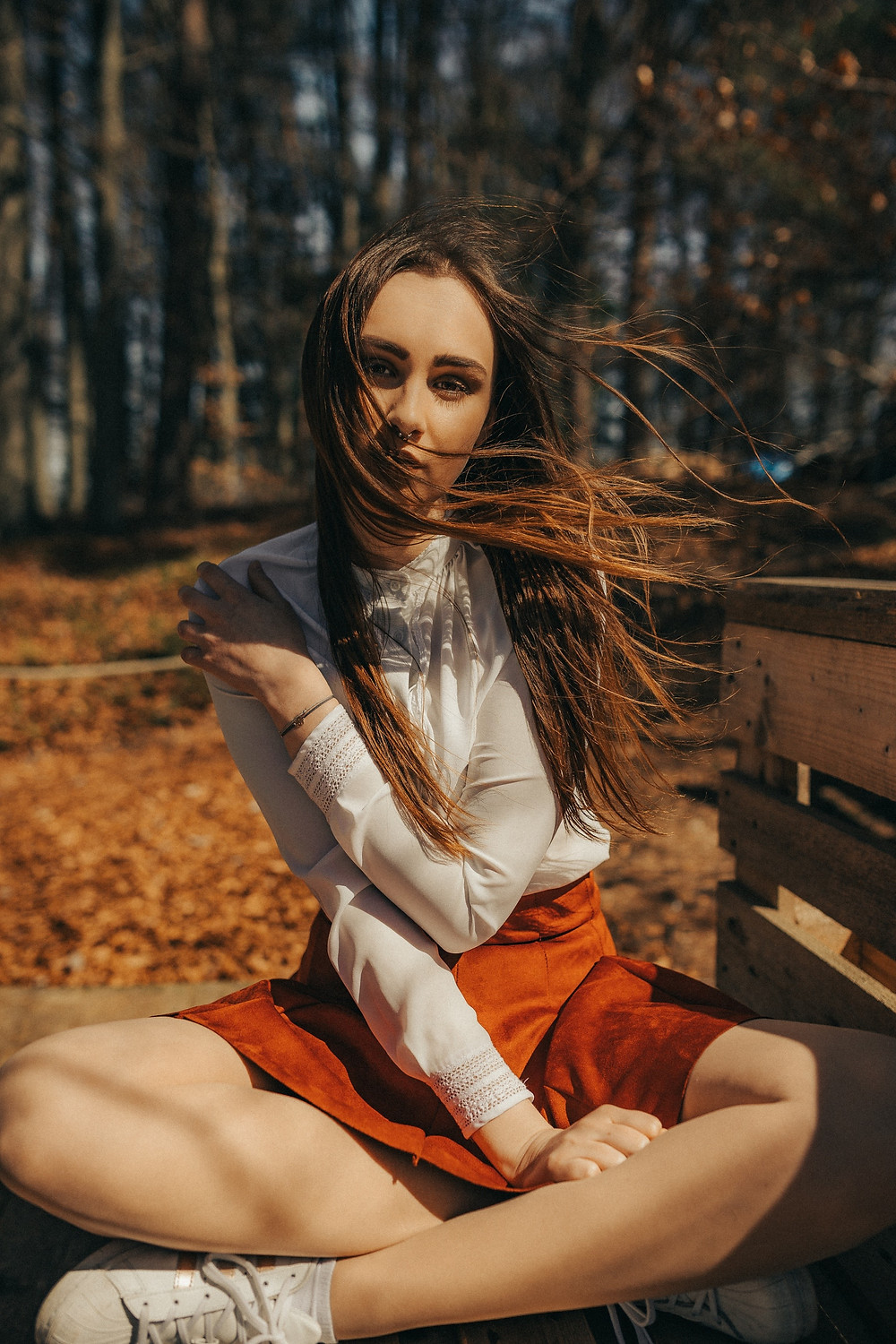 Lady sat in forest with long brown hair flowing in the breeze