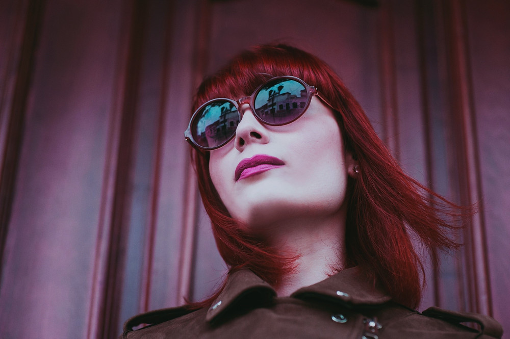 Lady with shoulder-length red hair and sunglasses