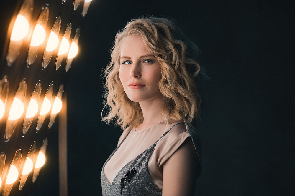 Attractive lady with citrine blonde hair stood in front of a selection of lights