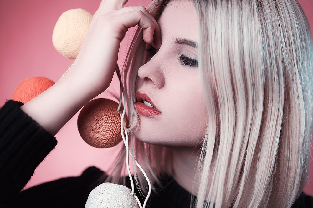 Blonde lady model touches her shoulder length hair in front of baubles
