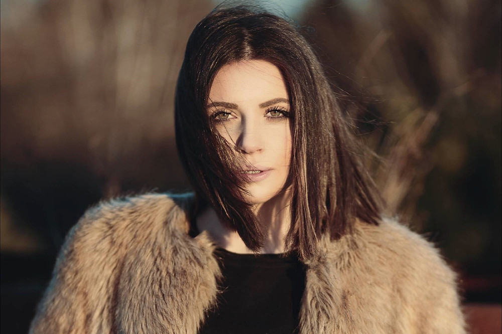 Lady with deep chocolate-coloured shoulder length hair poses in a fur coat