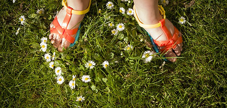feet wearing orange sandals standing in grass an flowers