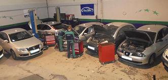 foto de coches con capos de rmoto abiertos dos mecanicos haciendo reparacion y tres caros de heramienta con un elevador y cartel de eurotaller foto esta hecha por parte ariba en talleres dyd