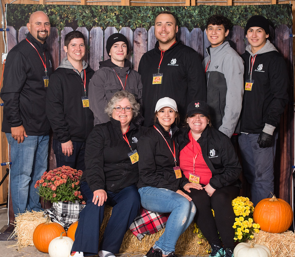 Group of people sitting on hay bales with orange pumpkins and yellow flowers for decoration