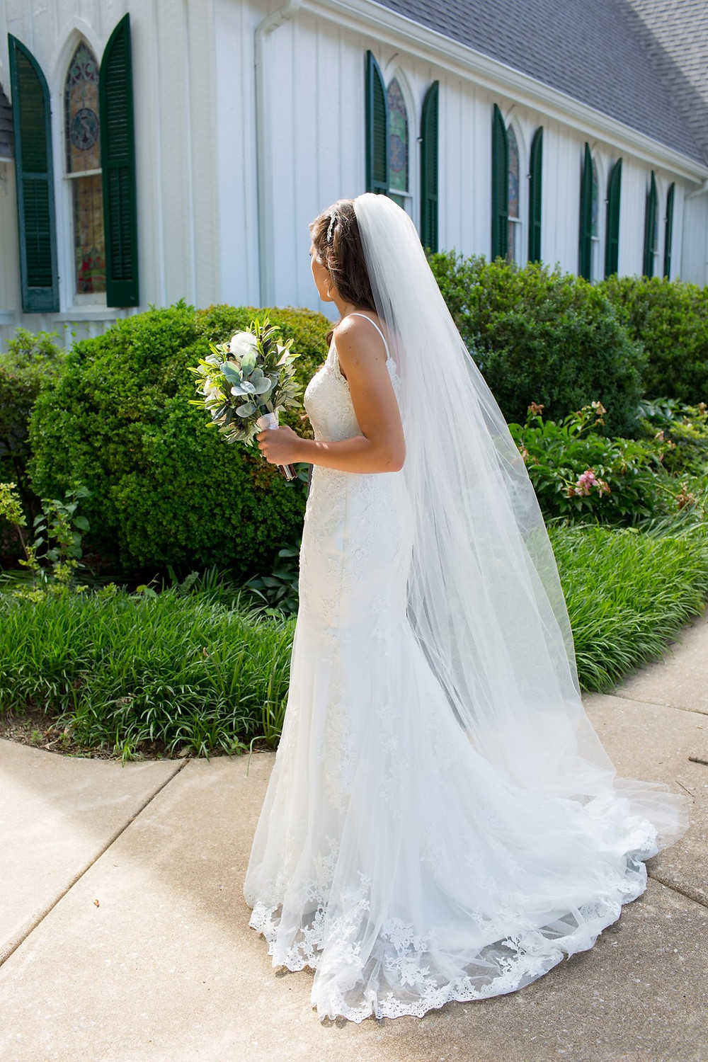 A bride stands at the corner of St. Mark's Episcopal Church and looks in. She is wearing a long veil and holding her bouquet