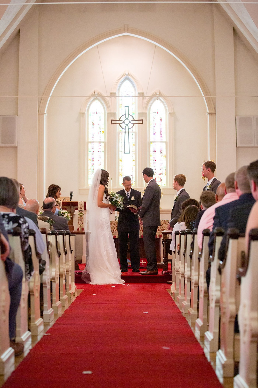 Ceremony at St Mark's Episcopal Church. Red isle runner and you can see some guests and the bride and groom as they stand at the front of the church