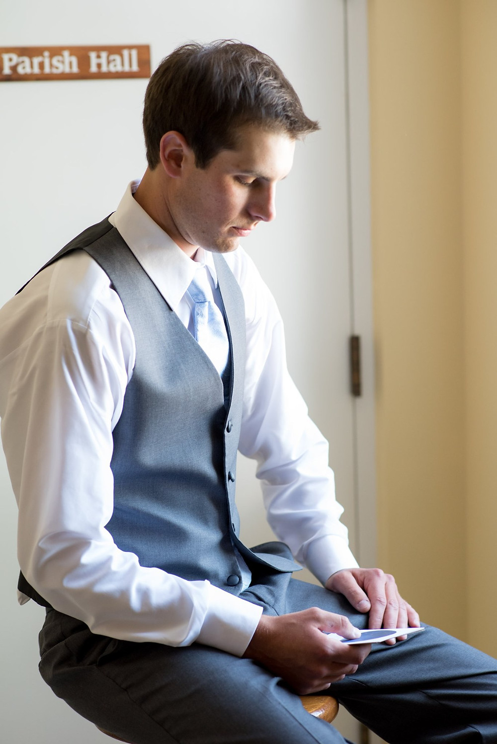 Groom is sitting on a stool looking at a letter he is holding in his and. He is not wearing a jacket but he is wearing suit bottoms, a vest and a blue tie