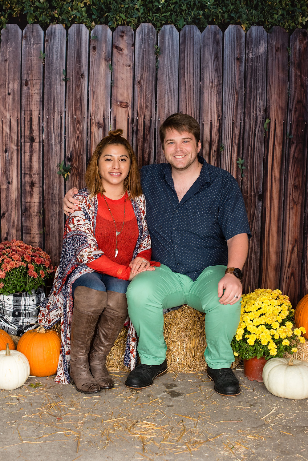 Couple sitting on hay bales surrounded by orange pumpkins and yellow flowers