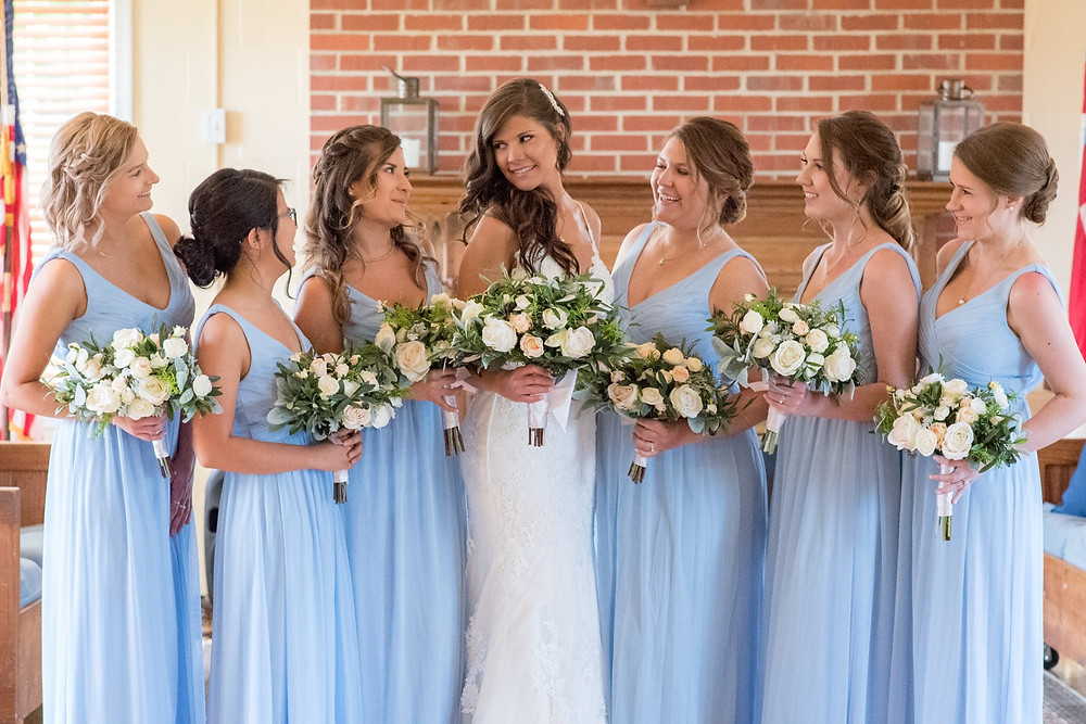 St Mark's Episcopal Church. Six bridesmaids in blue are all looking lovingly at the bride