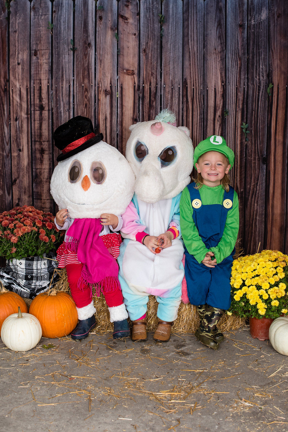 Group of costumed children on hay bales. One is wearing a snowman head, one is wearing a unicorn head and one is dressed as a Mario Brothers character