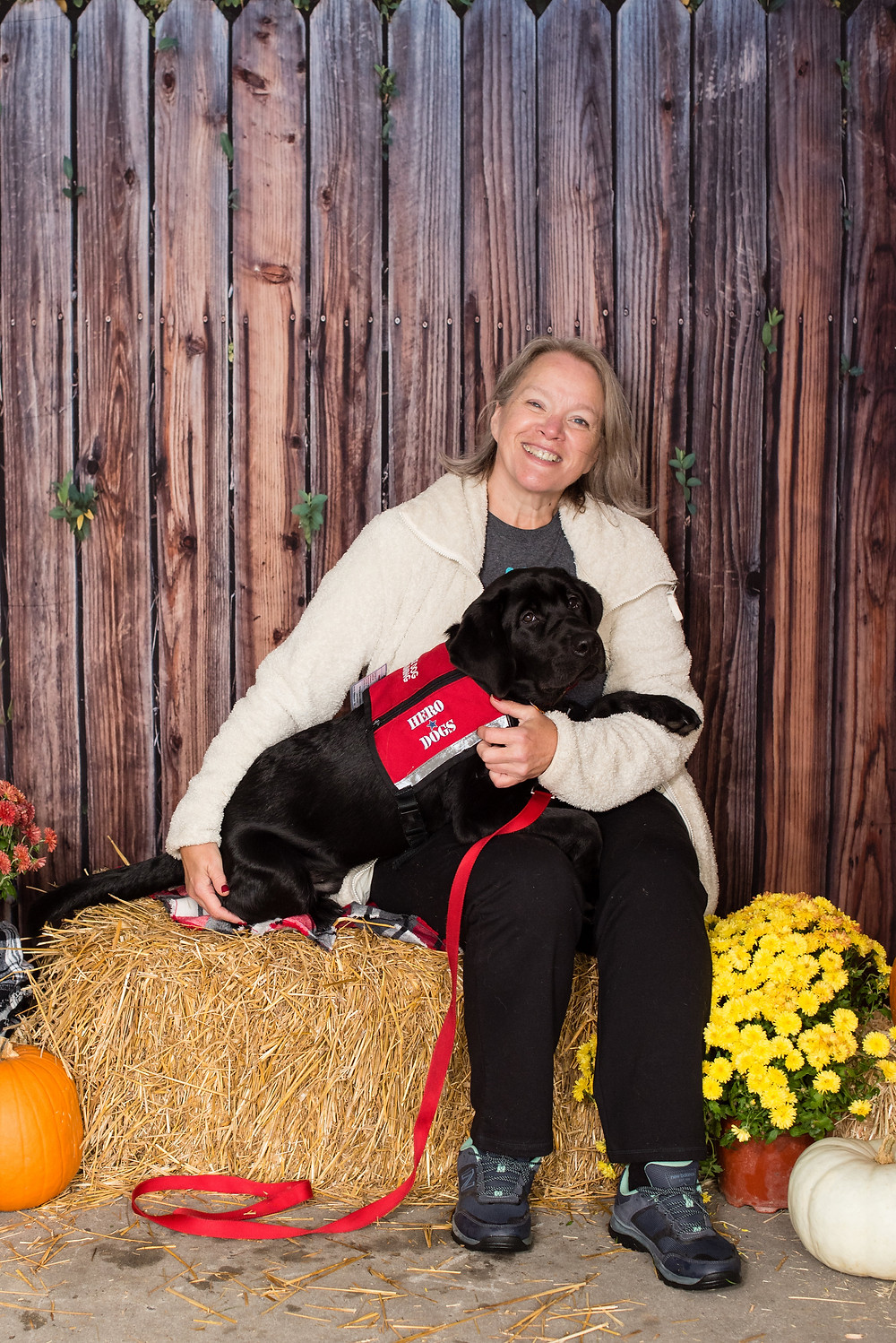 Smiling lady and her black Labrador Retriever are sitting on a hay bale surrounded by orange pumpkins and yellow flowers
