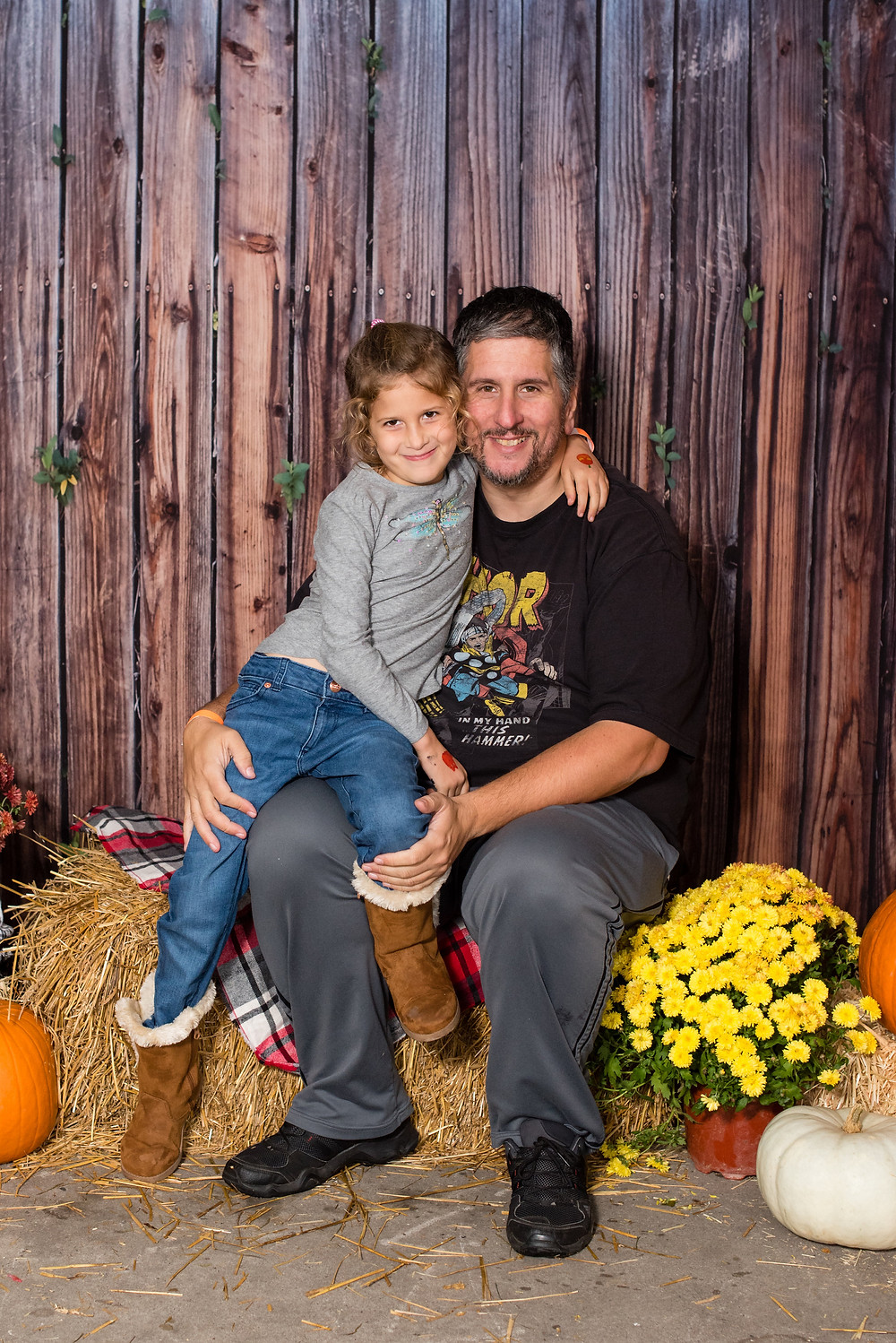 Father and daughter are sitting on hay bales and smiling at the camera.