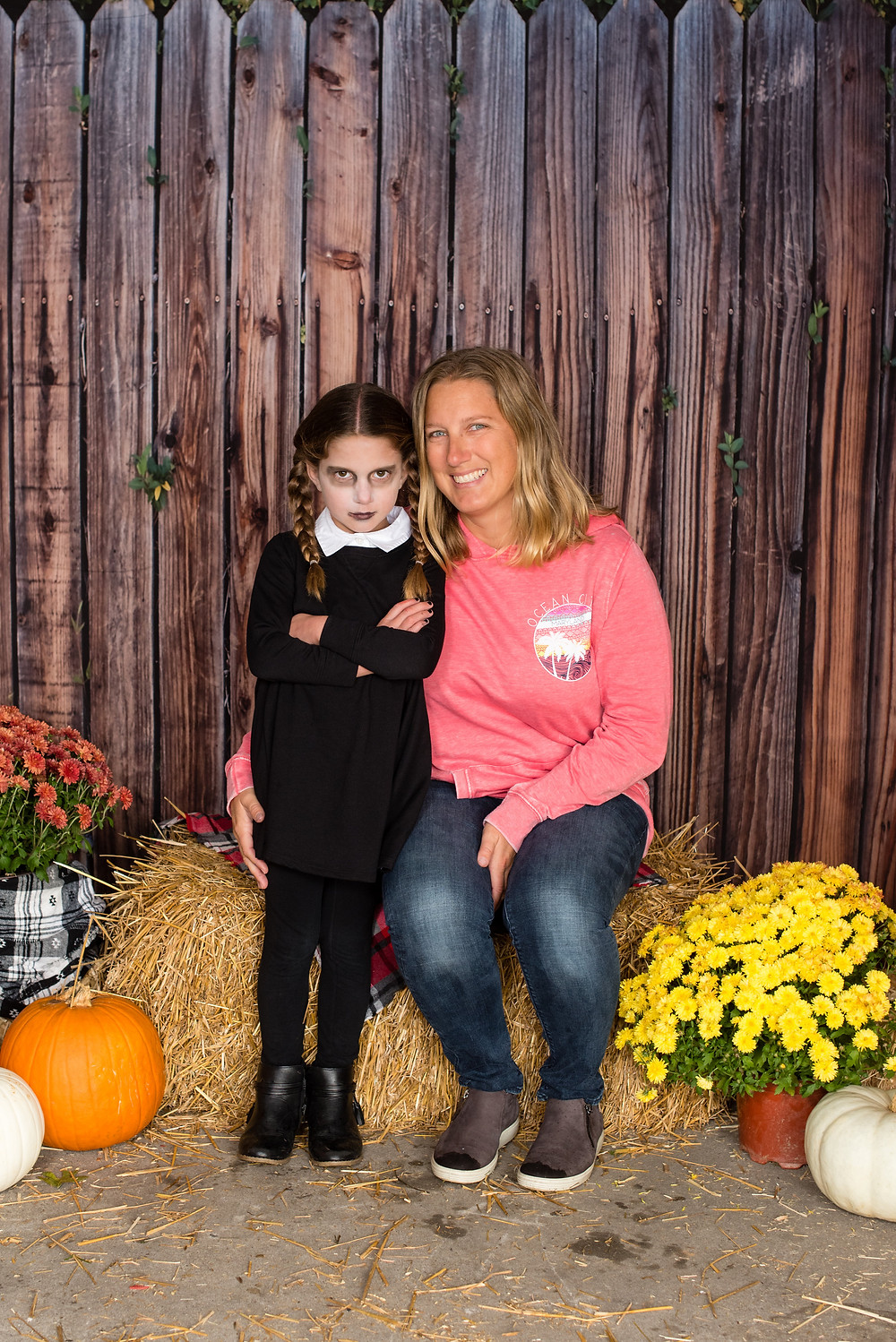 A mother and daughter sitting on hay bales with orange pumpkins and yellow flowers. Daughter is dressed as Adams Family character