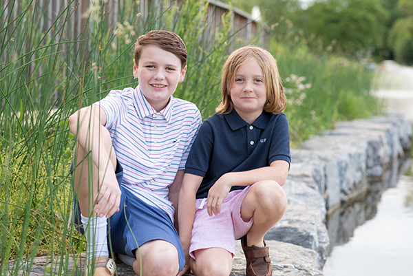 Two young boys are sitting by the edge of a creek looking at the camera. One is wearing a blue and pink striped shirt with blue pants and the other is wearing a navy shirt and pink pants. Both are smiling