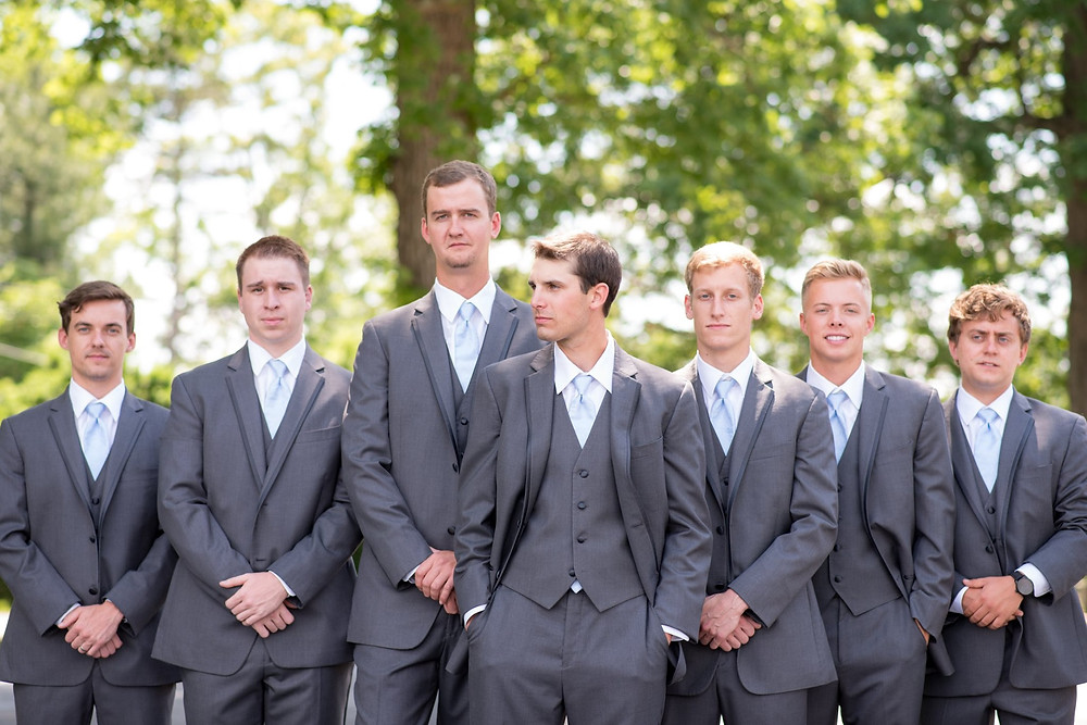 St Mark's Episcopal Church. Six groomsmen are dressed in gray and looking at the camera. Groom is in center looking away from the camera