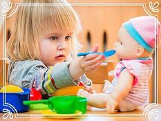 girl feeding baby doll