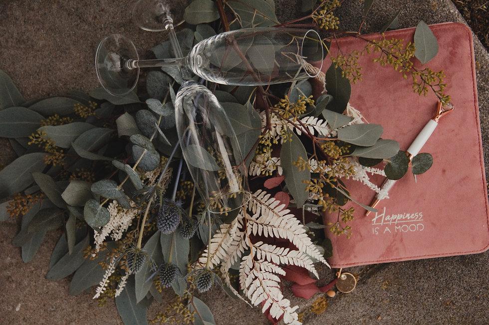 Dieses Bild zeigt das Titelbild Kroni-Moments Eventplanung aus Landshut in Niederbayern. Darauf zu sehen sind ein Brautstrauß aus Trockenblumen und Eukalyptus einer Hochzeit im Boho-Stil. Ebenfalls darauf abgebildet ist, das Notizbuch der Weddingplannerin Lisa Kronthaler, Gründerin von Kroni-Moments Eventplanung. Auf dem Hochzeitstitelbild abgebildet ist zudem der Leitspruch von Kroni-Moments Eventplanung / Hochzeitsplanung. Der Spruch lautet: ,,Lasst uns gemeinsam Momente erschaffen''.