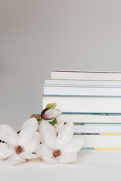 stack-of-books-near-magnolia-flower-on-t