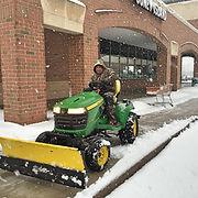 plowing sidewalk with john deer tractor