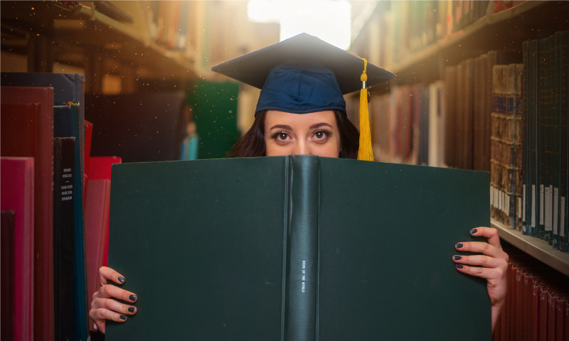 High school graduate holding book in library