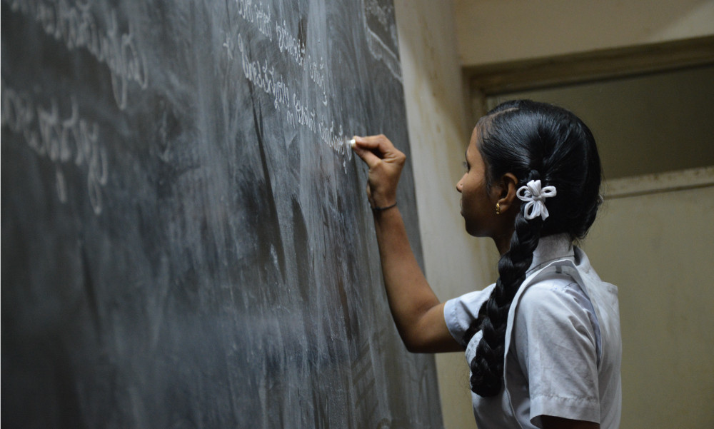 Student completing math equation at chalkboard