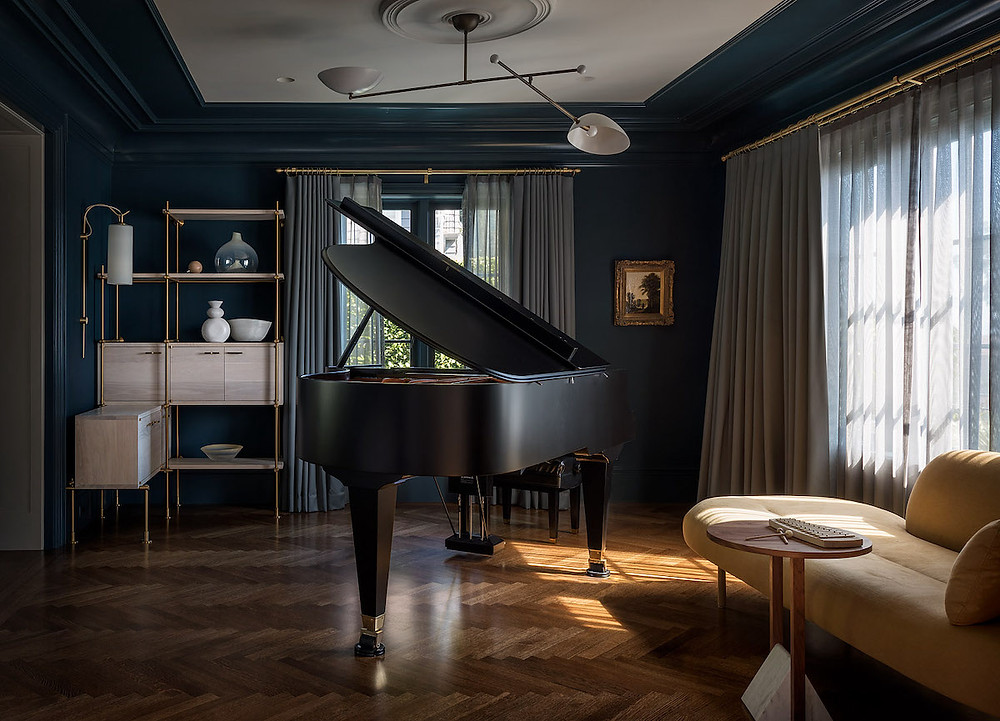 grand piano in dark room, herringbone wood floors, longe with side table, dark green walls, modern sconce, moderating bookshelf, draperies moody interiors
