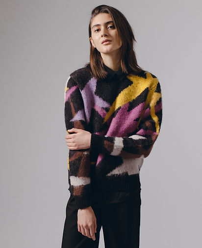 Maiden Noir and Sno-Valley mushrooms. Seattle clothing brand, drops its A/W 2020 line, drawing colors, shapes, and relaxed silhouettes from the fascinating world of mycoflora. Model in colorful sweater with purple, gold, brown, pink, black pants, mid-length brown hair on gray background