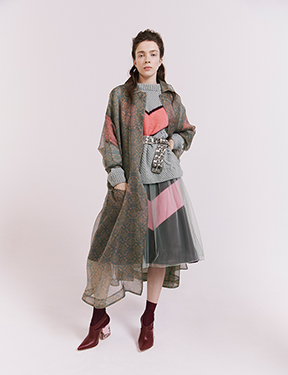 a patterned organza coat tops a tulle dress, leather skirt, and knit sweater