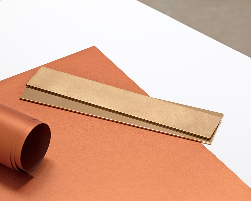 Modern level on table with orange and white paper