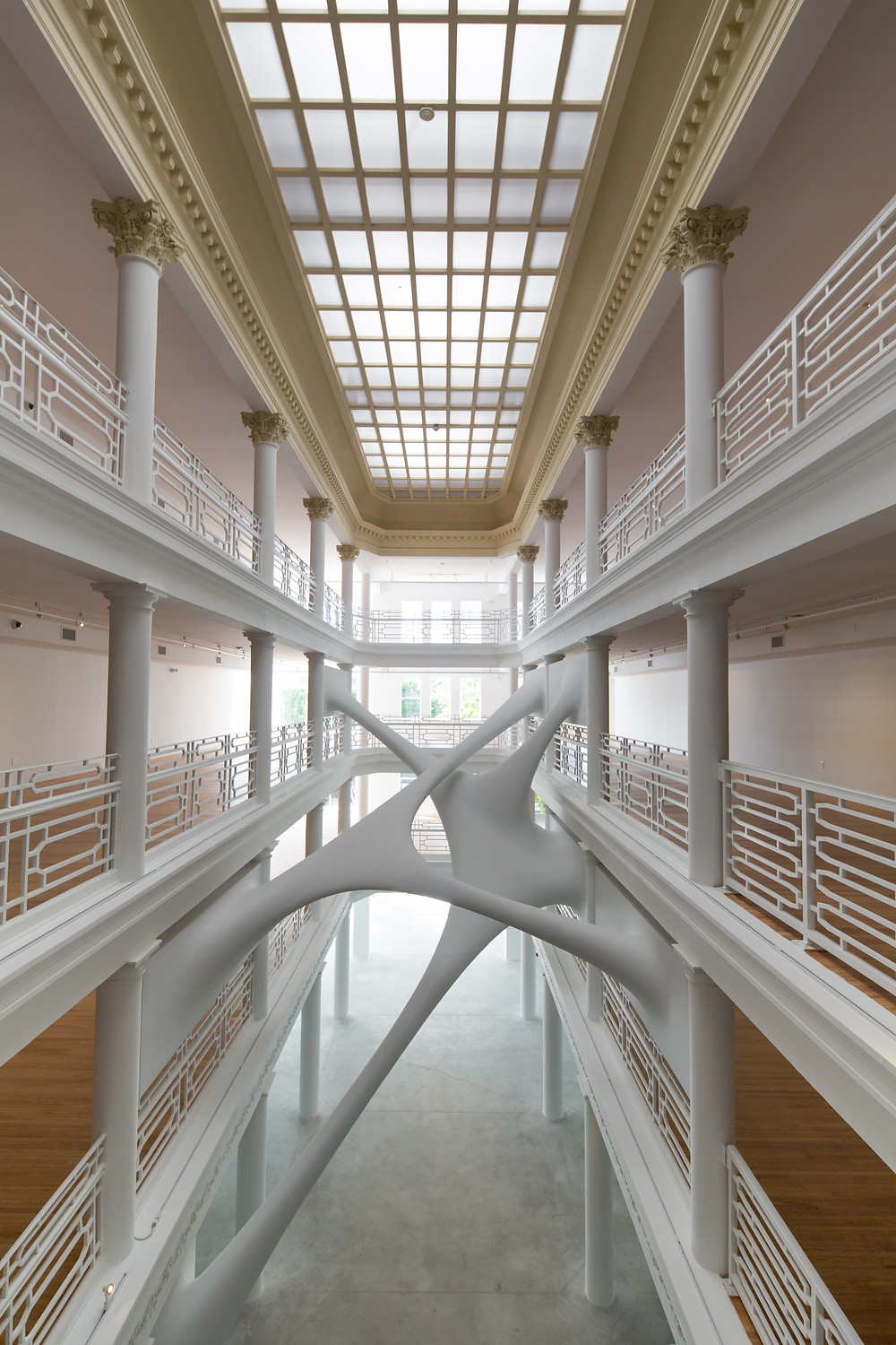 Four story atrium with glass ceiling, white columns and rails, light pink walls, concrete floor and abstract art in the middle. Moore Building Elastika by Zaha Hadid: Courtesy of Luis Gomez