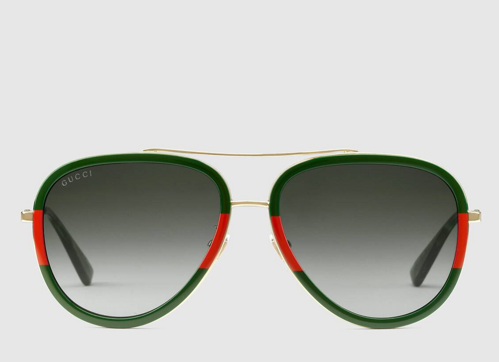 Gucci's gold metal with green and red web frame, green gradient lenses, gold brow bridge, nose bridge, and nose pads, black tips, on gray background