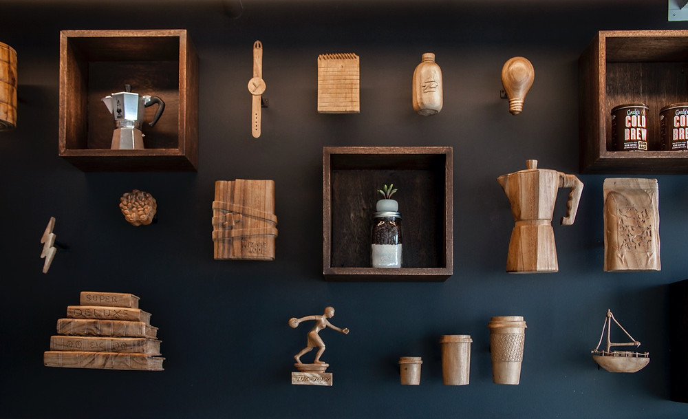 Black will with display of coffee and Seattle-themed carved wood figures including percolator coffee pot, lightbulb, watch with strap, stack of books, lightening, bowling trophy, Coffee cups with lids, brain, bottle, sailboat