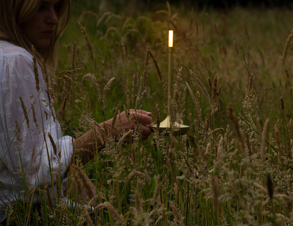 Woman in grassy field with candlestick light
